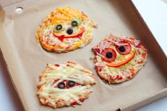 Halloween creative scary food monster zombie face with eyes pizza snack with mozzarella, basil and sausage in craft box. royalty free stock images