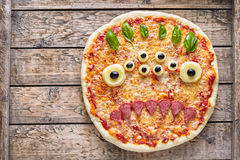 Halloween creative scary food monster zombie face with eyes pizza snack  mozzarella, basil and sausage Stock Image