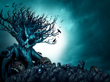 Halloween Creepy Background. Haunted ghost tree at night as an old growth plant shaped as a monster skull with pumpkins and spiders as a scary blue autumn Royalty Free Stock Images