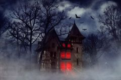 Haunted Halloween house. Halloween creepy house with bats and red light from the windows, Halloween theme Royalty Free Stock Images