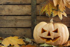 Halloween creepy pumpkin. Creepy carved pumpkin face on wooden bacground and autumn leafs Stock Photos