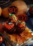 Halloween Cucpcakes con la decorazione del cappello a cilindro del testo e la crema arancio Candele e fondo della zucca Immagine Stock