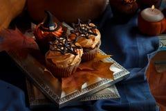 Halloween Cucpcakes con la decorazione del cappello a cilindro del testo e la crema arancio Candele e fondo della zucca Fotografia Stock