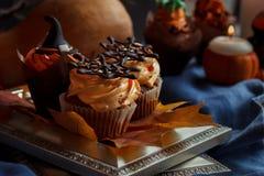 Halloween Cucpcakes con la decorazione del cappello a cilindro del testo e la crema arancio Candele e fondo della zucca Fotografia Stock Libera da Diritti
