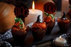 Halloween Cucpcakes con la decorazione del cappello a cilindro del testo e la crema arancio Candele e fondo della zucca Fotografie Stock