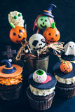 Halloween cup cakes and cake pops. Funny delicious cake pops and cup cakes for Halloween on the table,selective focus Royalty Free Stock Images