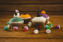 Halloween cup cakes and candies on table. Halloween cup cakes and candies on wooden table Stock Images