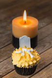 Halloween cupcake and candle on rustic table Royalty Free Stock Images