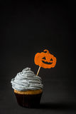 Halloween cupcake with pumpkin on black background Royalty Free Stock Photo