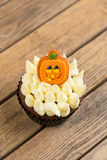 Halloween cupcake with pumpkin cake topper on an old rustic  wooden table Royalty Free Stock Photos
