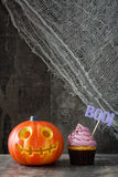 Halloween cupcake and pumpkin on rustic wooden background Royalty Free Stock Image