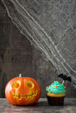 Halloween cupcake and pumpkin on rustic wooden background Royalty Free Stock Photo