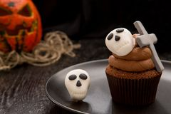 Halloween cupcake with tombstone cross and skulls. Cupcake with pumpkin. Halloween cake on dark wooden table. Close up Stock Photo