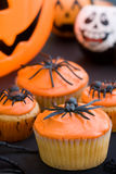 Halloween cupcakes. Cupcakes decorated with orange frosting and spiders Stock Photos