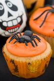 Halloween cupcakes. Cupcakes decorated with orange frosting and spiders Royalty Free Stock Photos