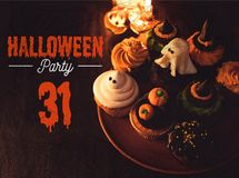 Halloween cupcakes and burning candles. Close-up view of traditional halloween cupcakes and burning candles in black stock illustration
