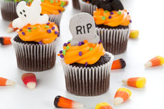 Halloween cupcakes. Halloween cupcake with RIP, ghost, and bat decorations surrounded by Halloween cupcakes, corn candies, and decoration Stock Photography