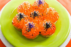 Halloween cupcakes decorated with toy plastic spiders Royalty Free Stock Image