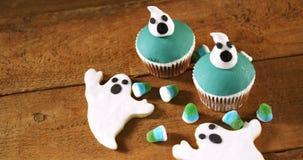 Halloween cupcakes en peperkoekkoekjes op een houten lijst 4k stock videobeelden