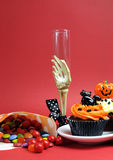 Halloween cupcakes, skeleton glass and candy treats on red background - vertical. Stock Images