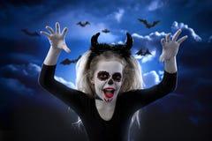 Halloween, días de fiesta, concepto de la mascarada - el retrato de la pequeña muchacha hermosa joven con maquillaje del cráneo e imagen de archivo