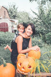 Halloween. Daughter hugging mother near jack-o-lantern in the garden. Decoration for party. Happy family. Toned photo. stock photo