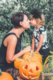 Halloween. Daughter and mother kisses near jack-o-lantern in the garden. Decoration for party. Family. Toned photo royalty free stock image