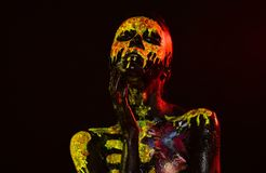 Halloween day of dead celebration. Woman skeleton with flower on chest. Body painting and art. Life and death concept. Girl with skull face paint on black royalty free stock images