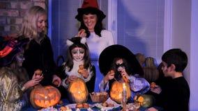 Halloween De kinderen en de ouders nemen verfrissingen van de feestelijke lijst stock videobeelden