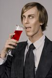Halloween Death is on its way!. Handsome young vampire drinking form Champaign glass stock image