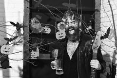 Halloween decor on background Demon with horns and wild face holds black electric guitar. Halloween party concept. Devil or monster partying. Man wearing scary royalty free stock image