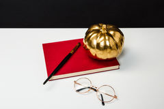Halloween decor on white table over black background. Royalty Free Stock Images