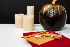 Halloween decor on white table over black background. Royalty Free Stock Photos