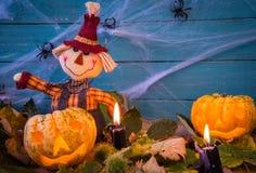Halloween-decoratie met vogelverschrikkerpompoenen en kaarsen Royalty-vrije Stock Foto