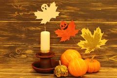 Halloween Decoratieve multicolored pompoenen dichtbij een ceramische kandelaar met een witte kaars en vliegende schadelijke spoke royalty-vrije stock foto's