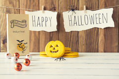 Halloween. Decoration background: a trick or treat paper bag, spiders, some pumpkins and eyes. Happy  is hanging on a rope with clothespins. Vintage Style royalty free stock images