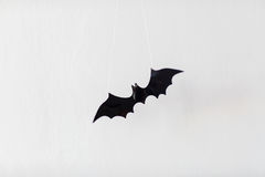 Halloween decoration of bat over white background. Halloween, decoration and scary concept - black flying bat hanging on strings over white background Royalty Free Stock Photo