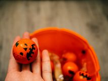 Halloween and decoration concept: Hand picking chocolade chocolates in an orange pumpkin stock photos