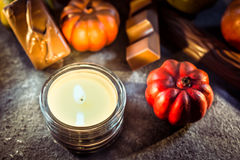 Halloween Decoration With One Candle Light, Chocolate And Pumpkins On Slate Stock Photo