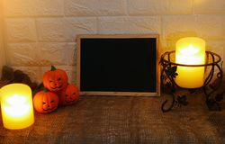 Halloween decoration pumpkins and candles with copy space black board on wall background Stock Images