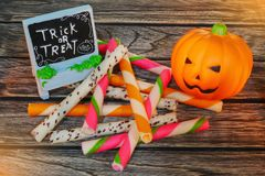 Halloween decoration trick or treat , jack-o-lantern pumpkin with snack on wooden background Stock Photo