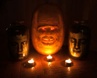 Halloween Decorations. Close-up of a carved pumpkin and two jars with head Stock Photo