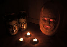 Halloween Decorations. Close-up of a carved pumpkin and two jars with head Stock Photography