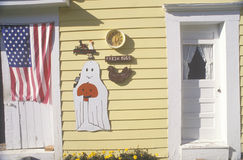Halloween decorations and an American flag on a yellow wooden house royalty free stock image