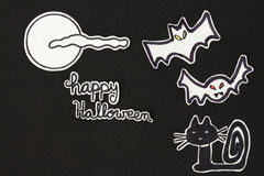Halloween decorations  cat, bats, moon, clound and Happy Hallowe. A horizontal overhead view of a Halloween scene: cat, bats with a moon and clouds and a happy Stock Photo
