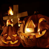 Halloween decorations. Closeup on scary Halloween decorations, eerie glowing carved pumpkin, eldritch spiders, cross and burning fire on graveyard, uncanny Royalty Free Stock Photos
