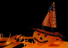 Halloween decorations. A cute, sparkly jack-o-lantern with pointy witch's hat covered with spider and web on black background with orange ribbon stock photo
