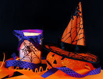 Halloween decorations. A cute, sparkly jack-o-lantern with pointy witch's hat covered with spider and web on black background with orange ribbon. Also, a spider royalty free stock photography