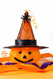 Halloween decorations. Cute, sparkly pumpkin with smiley face and witch's hate with orange and purple ribbons and curls and spider on white background ground stock photography