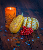 Halloween decorations, lit candle and pumpkins on a wooden table Stock Photos